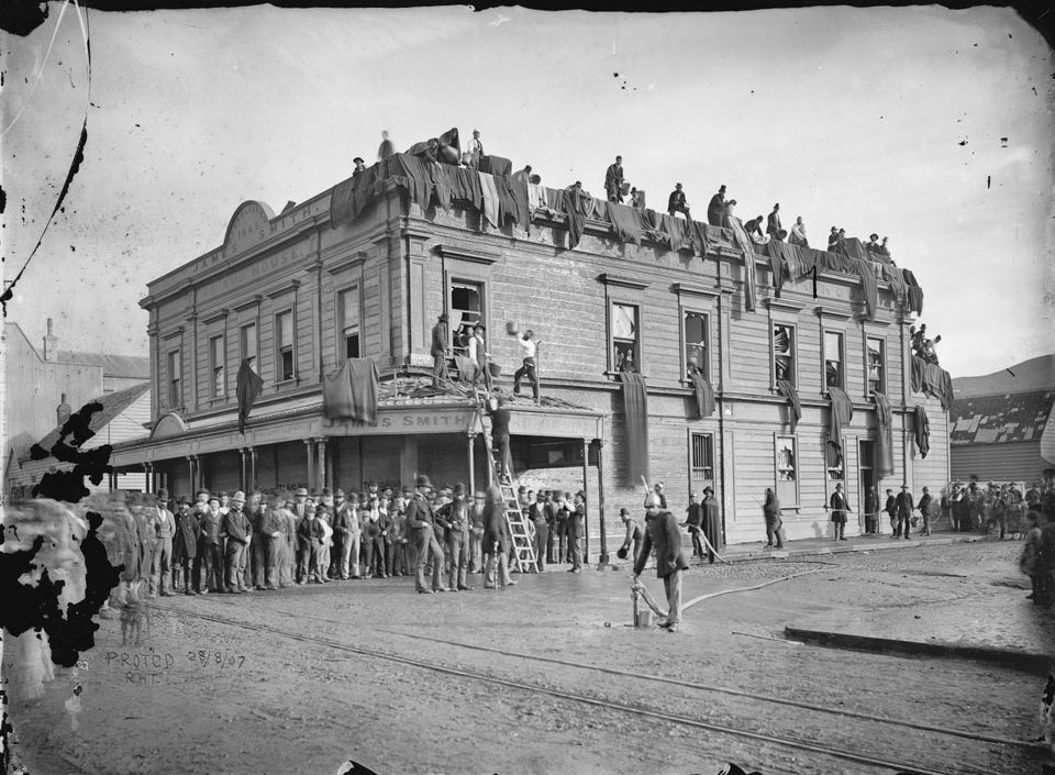 Black and white photograph of a house with people standing all around it, including the roof