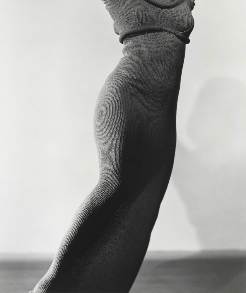 Photograph of a lady's torso in a long tight knitted dress