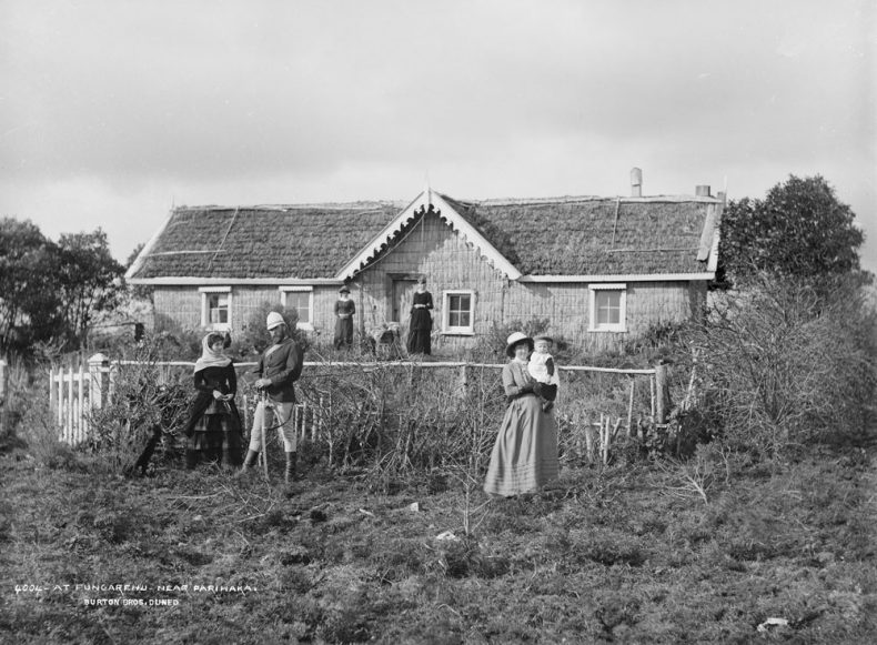Black and white photograph of a family outside a house