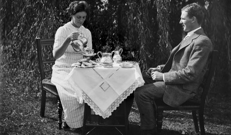 Man and woman sit at a table outside having tea