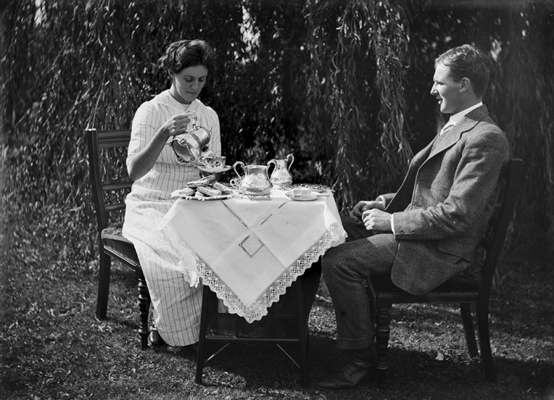 Maud Herd and Leslie Adkin sitting at a table in the garden. Maud is pouring tea.