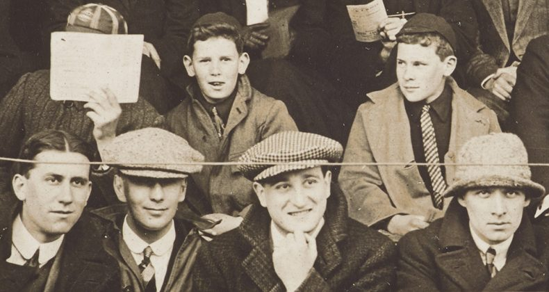 Boys sit in a grandstand with one hiding his face behind a sheet of paper