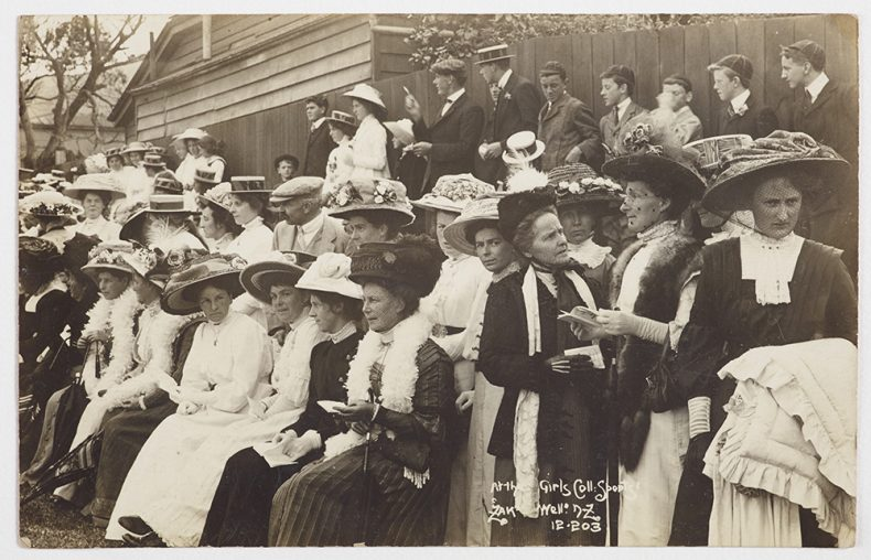 Group of women sitting watching sport, while men stand behind