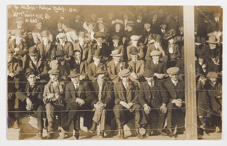 Men and women sit in a crowded grandstand