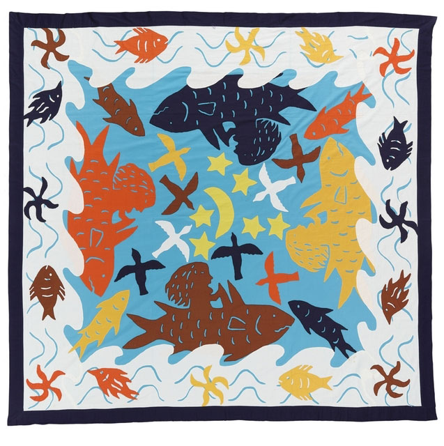 Brightly stitched quilt with a girl riding a whale