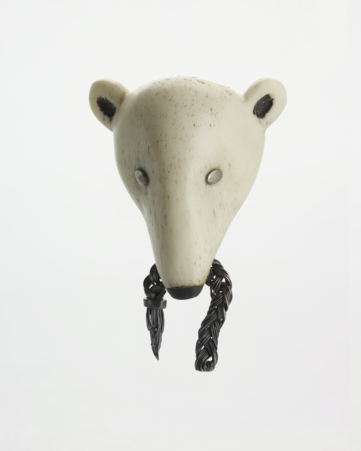Brooch resembling a polar bear's head with what appears to be a snapped piece of rope in its mouth