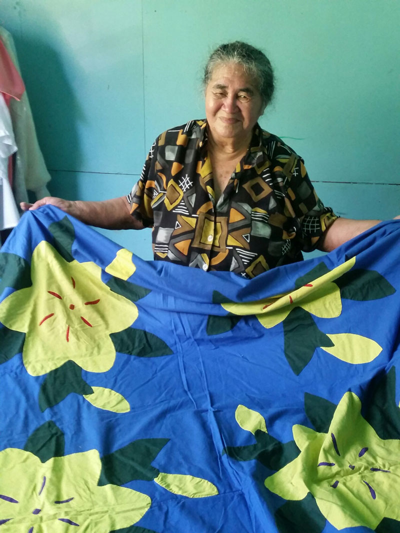 Mama Maria Teokota'I holds up a blue tīvaevae with yellow flowers