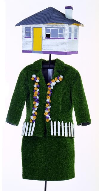 Mannequin adorned with a green coat resembling fake grass with a white picket fence belt and a house for a hat
