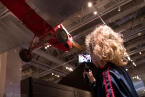 A girl films a plane hanging from the ceiling