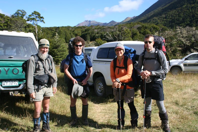 Four people in hiking gear stand in front of parked vehicles in the wilderness