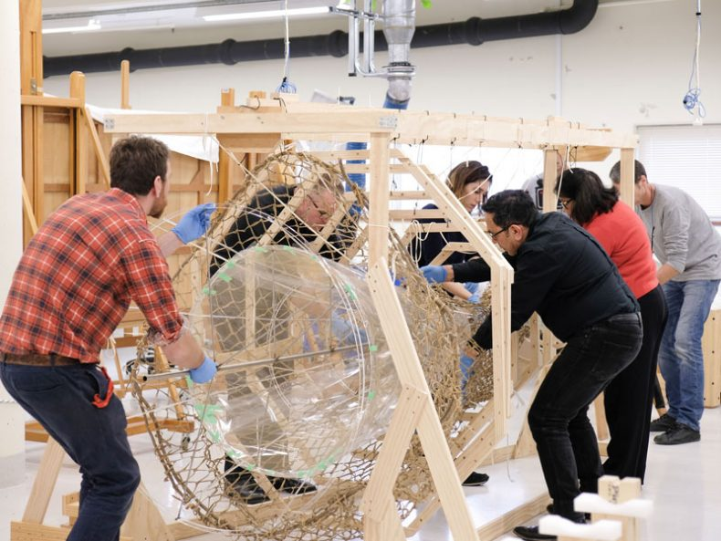 Callum (checked shirt) and the rest of the team insert a mount into a hinaki, 2017. Te Papa