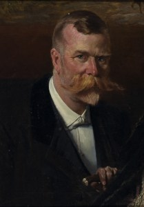 Bust portrait of a middle aged man, holding a walking stick in his left hand. He has blue eyes, a ruddy complexion and an abundant ginger moustache that extends beyond the side of his face.