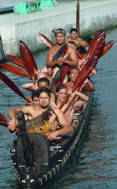 A waka being rowed in front of Te Papa
