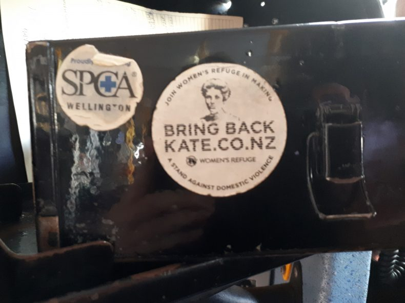 Photograph showing a white sticker on a black cash box. The sticker reads 'Join Women's Refuge in making a stand against domestic violence. Bring Back Kate.co.nz.' It also features a picture of Kate Sheppard.