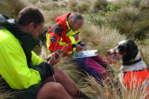 Colin Miskelly (on left, holding a snipe) and James Fraser teaching Percy the dog what snipe smell like, Enderby Island, January 2006. Photo by Andy Maloney