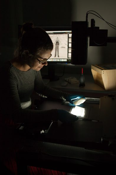 A person digitising the a negative