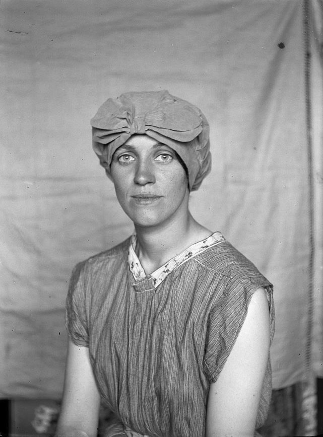 Black and white photograph of a woman wearing a cap looking intensely at the camera