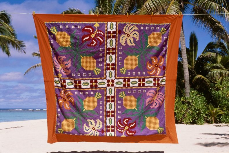 Tivaevae (quilt) hanging on a line with palm trees in the background