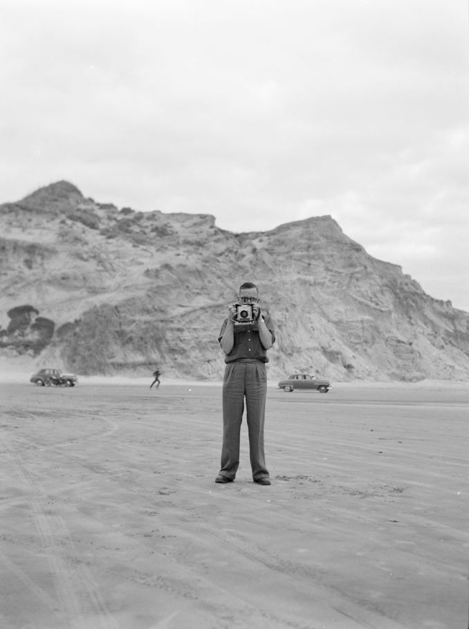 A black and white photograph of a man in a desolate landscape holding a camera