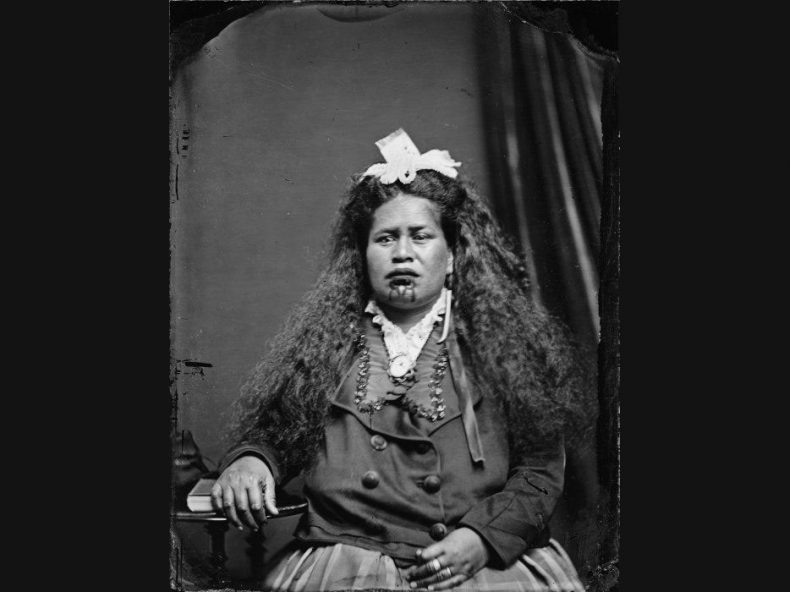 Black and white photo of a Māori woman wearing European clothes