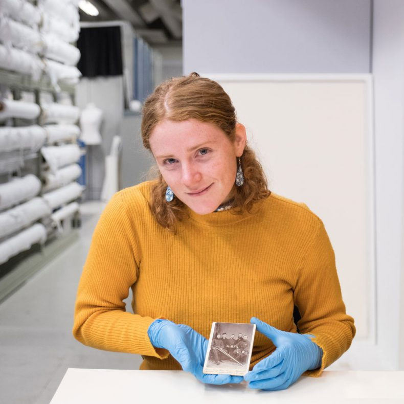 Caitlin holds a photograph in the photography storeroom