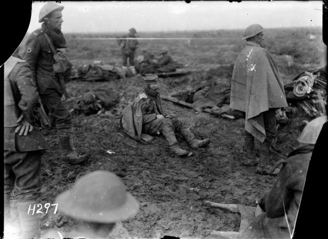 A badly wounded German prisoner sits on the ground awaiting medical treatment. Photograph taken in the Somme area 1917 by Henry Armytage Sanders. H297. Ref: 1/2-012942-G, Alexander Turnbull Library Wellington.