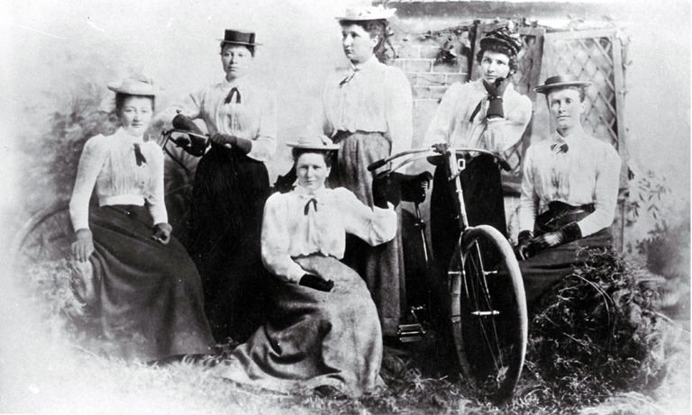 Black and white photo of a group of ladies with their bicycles