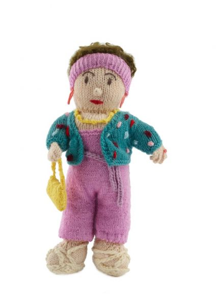 Knitted doll wearing pink pants, a green cardigan, a pink headband, and carrying a yellow purse