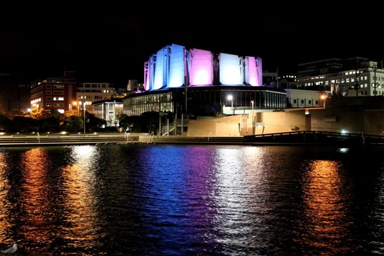 View of Michael Fowler centre across the Whairepo Lagoon, with alternating blue and pink lights covering the entire building