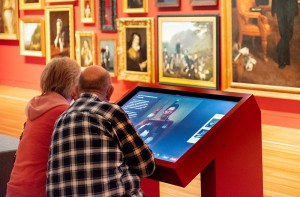 A couple use a digital label in a gallery