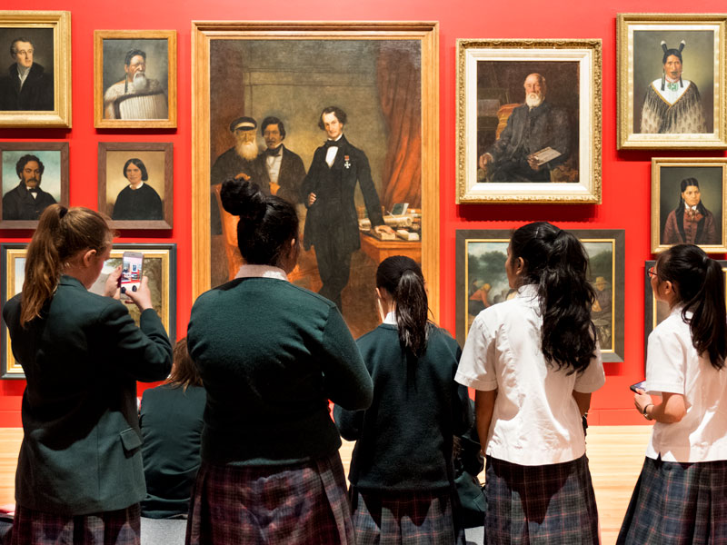 Students look at the portrait wall