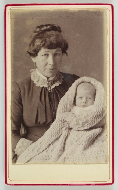Portrait of woman holding a baby wrapped in a blanket