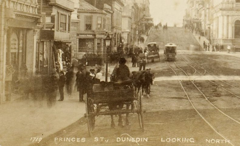 A stationary horse-drawn cart sits on a street while people mill about beside it