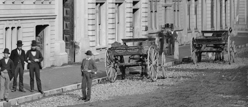 Men stand on a street with a horse-drawn cart parked by a building