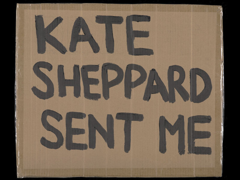 Cardboard placard with the words 'Kate Sheppard Sent Me' painted in black