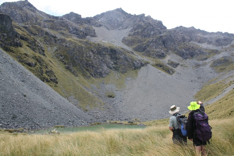 Botanists Brian Rance and Dave Toole arriving at the tarn at Hummock Peak, Southland, and indicating we still have more climbing to do if we want to get to the forget-me-nots... Photo by Heidi Meudt @ Te Papa.
