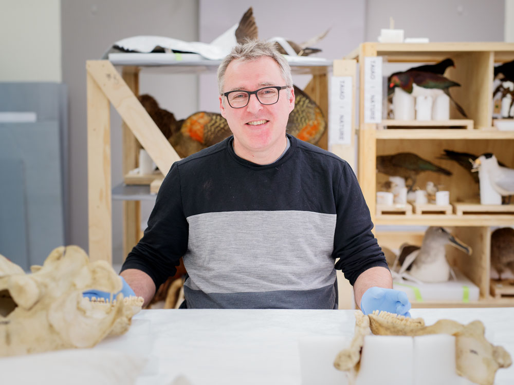 Conservator Robert Clendon smiles in front of specimens including whale skulls and taxidermy birds