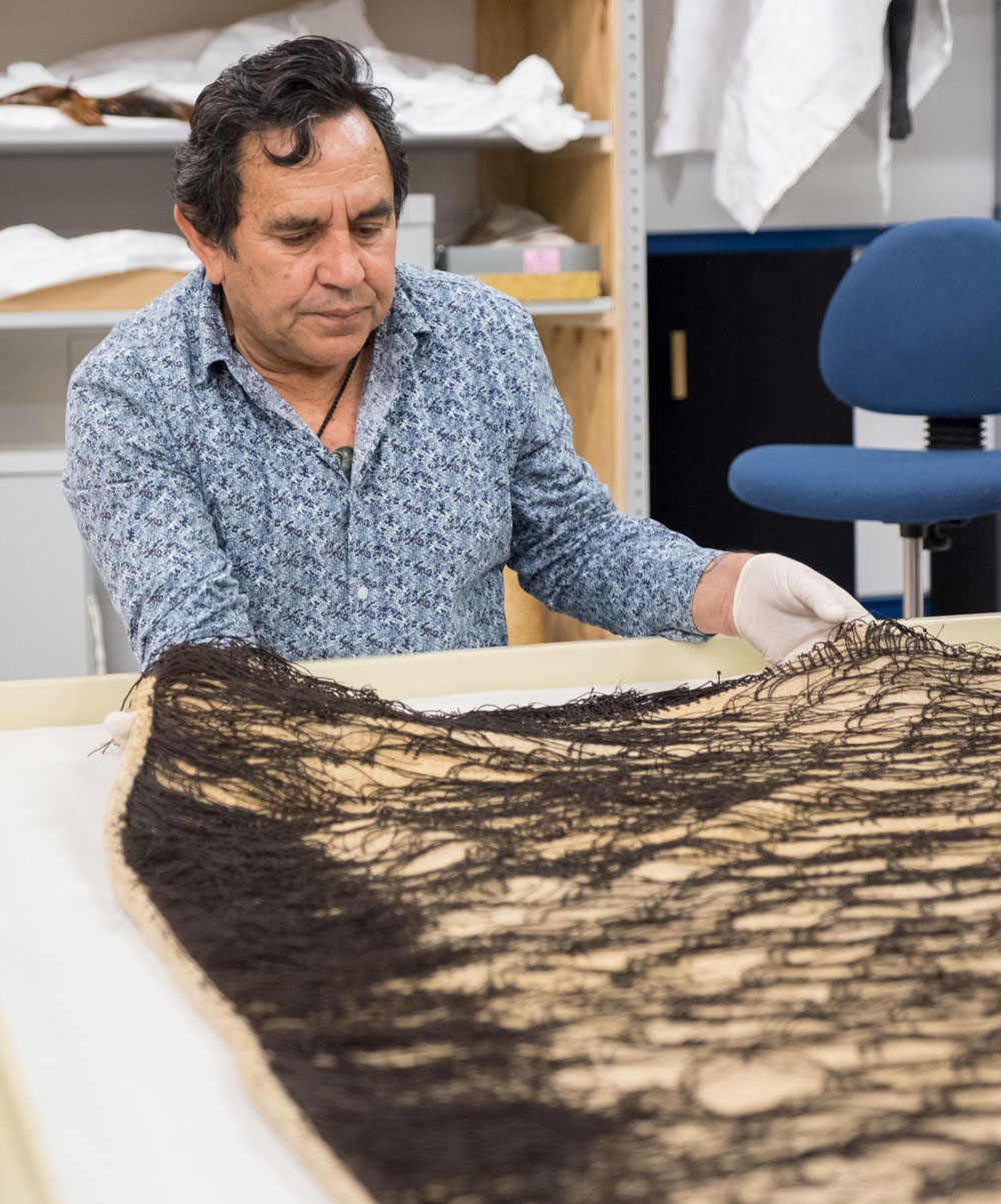 A man looks at a Māori in a museum storeroom