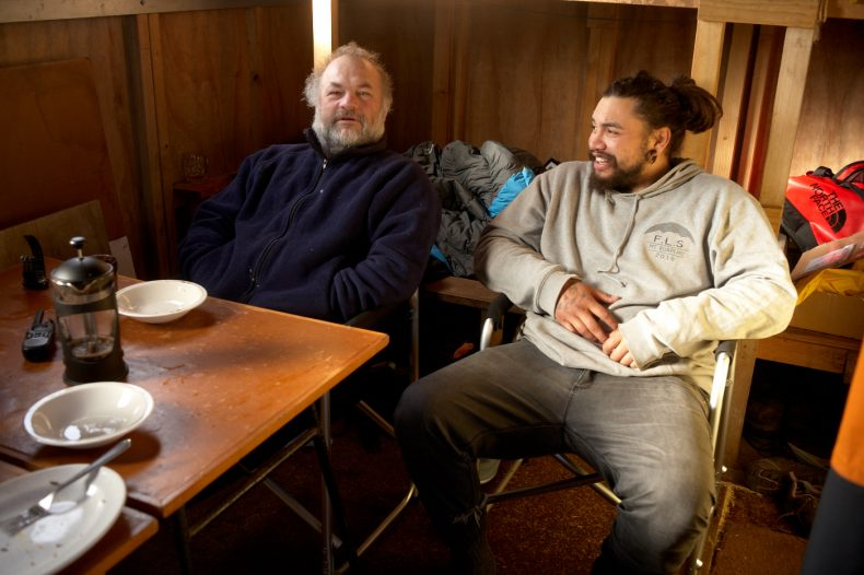 Two men sit in chairs in a cabin with plates and a coffee pot on the table in front of them