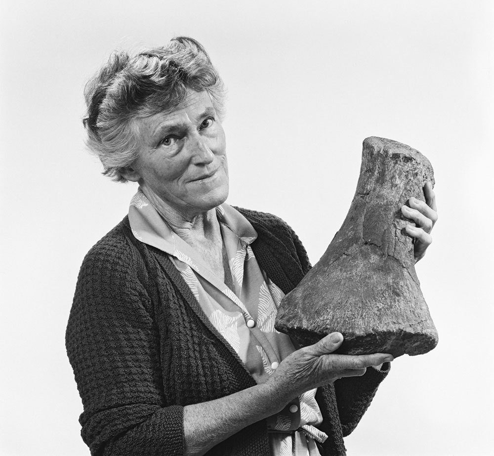 A lady holds a large dinosaur bone