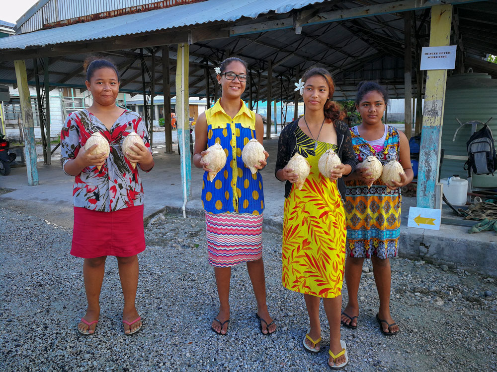Young girls holding coconuts. They're wearing bright floral dresses