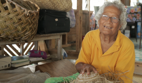 A lady in a yellow shirt holds up some of her weaving