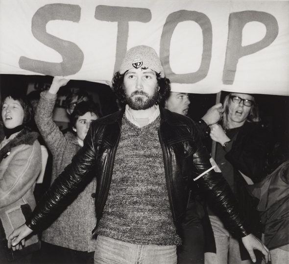 Man with arms outstretched stands in front of a sign saying 'Stop'
