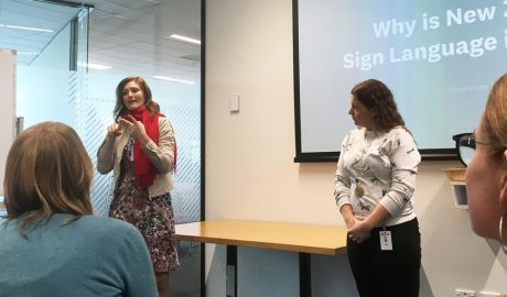 Two ladies using sign language in front of a group