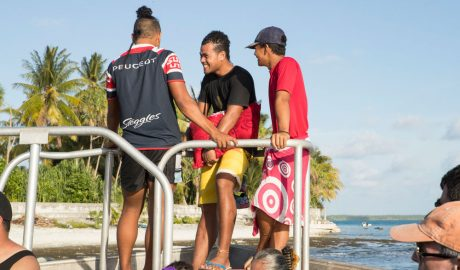 Teenagers laughing on a boat. Palmtrees and the sea can be seen in the background