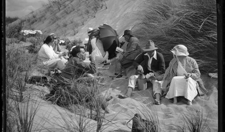 Black and white photograph of a group of people sitting in sand dunes, eating and drinking.