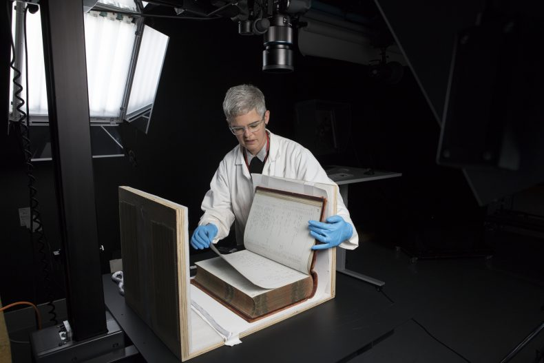 Imaging technician setting up a large book for photographing in a photography studio.
