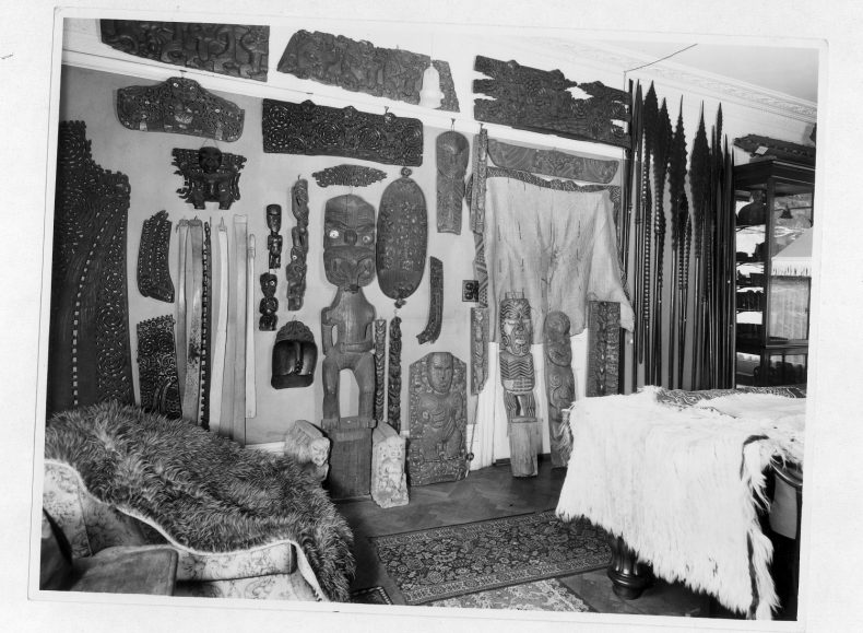 Room filled with Māori carvings, feather cloaks and paddles.