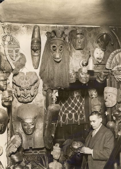 Image shows room filled with various masks and headresses of African and Pacific origin.