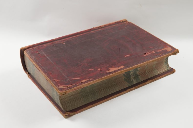 Worn leather bound book, with gold letters spelling out 'Ledger' on the spine.